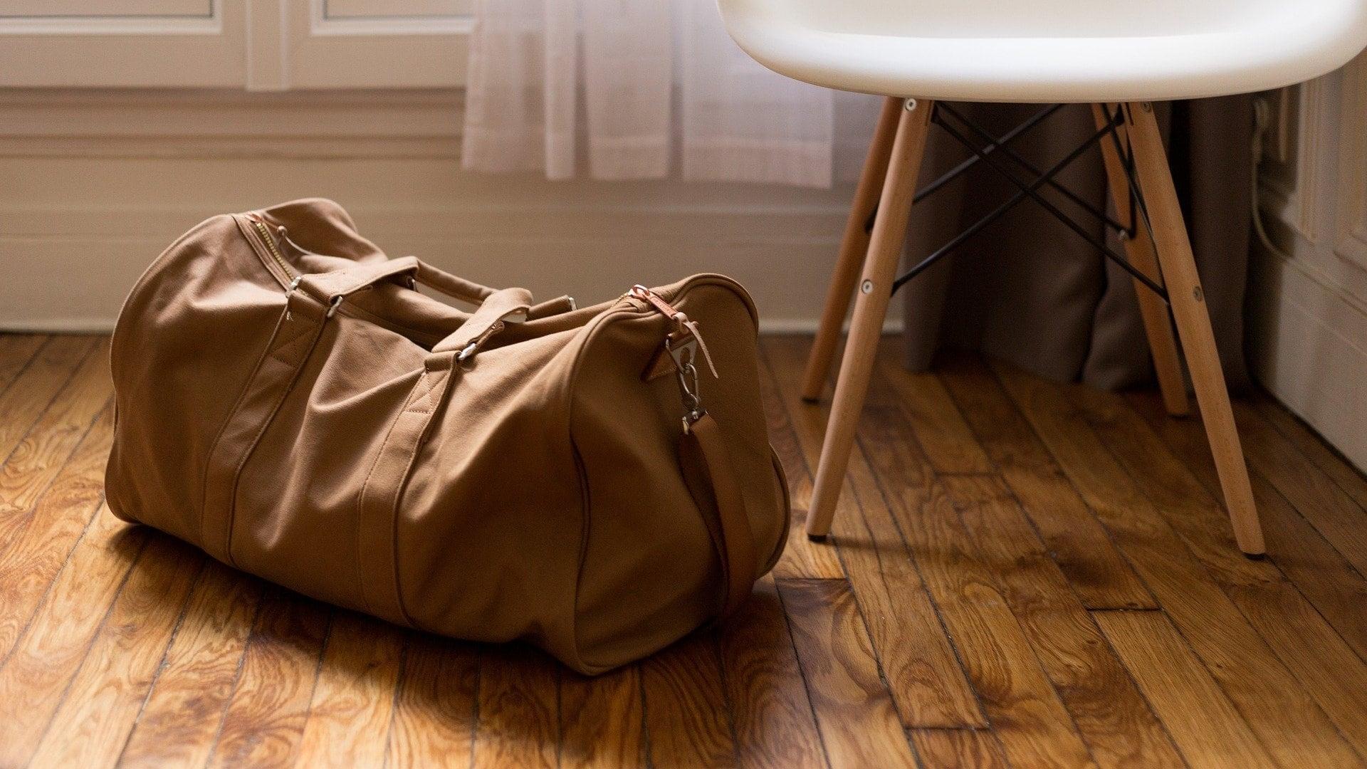 Braune Reisetasche steht auf einem Holzboden